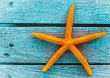 Pomarańczowa rozgwiazda lub denna gwiazda na błękitnych drewnianych deskach Fotografia Royalty Free