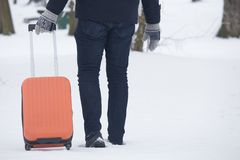 Pomarańczowa walizka na kołach i mężczyzna nogach w śniegu fotografia royalty free