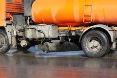 Pomarańczowa zbiera maszyna myje samochodową drogę w wiośnie Zdjęcia Royalty Free