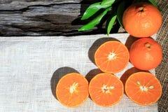 Pomarańczowe mandarynki lub tangerine owoc z zielonymi liśćmi na drewnianej deski tle, zdjęcie stock