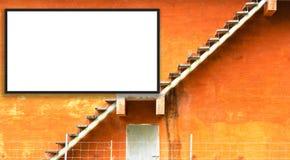 Pomarańczowego budynku i Pożarniczej ucieczki schodki na outside pusty billboardu biel Pusta przestrzeń dla teksta i wizerunków fotografia royalty free