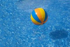 Pomarańczowego koloru żółtego błękitna barwiona piłka w basenie z błękitne wody obrazy royalty free