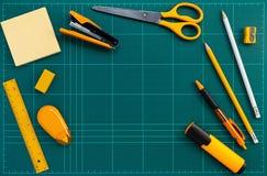 Pomarańczowego materiały biurowe dostawy na zielonej rozcięcie macie, mieszkanie nieatutowy obrazek zdjęcia stock