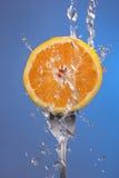 Pomarańczowego owocowego rozwidlenie wody pluśnięcia pojęcia błękitni zdrowie Zdjęcia Stock