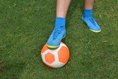 Pomarańczowej futbolowej piłki nożnej zielona trawa z gracza tła przestrzenią Zdjęcia Royalty Free