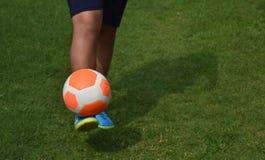 Pomarańczowej futbolowej piłki nożnej zielona trawa z gracza tła przestrzenią Zdjęcie Stock