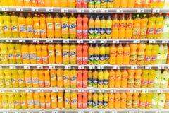 Pomarańczowej sody soku butelki Na supermarketa stojaku zdjęcia stock