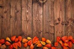 Pomarańczowi Chińscy lampiony & x28; Physalis& x29; na nieociosanym drewnianym stole Fotografia Stock