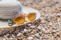 Pomarańczowi okulary przeciwsłoneczni i kapelusz na plaży Zdjęcie Royalty Free