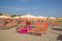 Pomarańczowi parasole i bryczka hole na plaży Rimini w Nim Obrazy Stock