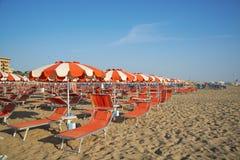 Pomarańczowi parasole i bryczka hole na plaży Rimini w Nim Zdjęcie Royalty Free