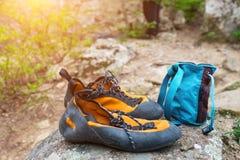 Pomarańczowi pięcie buty, magnez w błękitnej torby stojaku na kamieniu i Wspinaczkowa odzież zdjęcia stock
