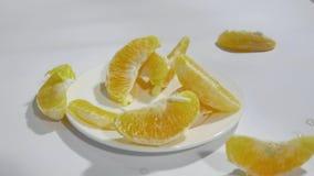 Pomarańczowi plasterki spadają na białym talerzu w zwolnionym tempie zbiory