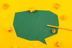 Pomarańczowi prześcieradła papier kłamają na zielonym zarządzie szkołym i tworzą gadka bąbel z ołówkiem, miącymi papierami i kopi fotografia stock