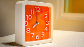 Pomarańczowy ścienny zegar na bielu stole Zdjęcie Royalty Free