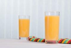 Pomarańczowy świeży sok obok wyśmienicie dojrzałych pomarańcz na stole Obrazy Royalty Free