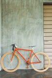 Pomarańczowy bicykl parkujący dekoruje wewnętrznego żywego izbowego nowożytnego styl Zdjęcia Royalty Free