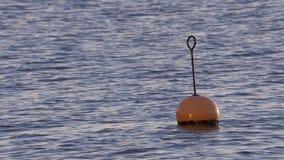 Pomarańczowy boja unosi się na ocean fala przy zmierzchem (zwolnione tempo 2) zbiory wideo