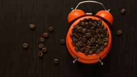 Pomarańczowy budzik z kawowymi fasolami na drewnianym stole zbiory wideo