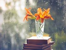 Pomarańczowy daylily kwitnie w wazie która stoi na książkach Okno z raindrops niebieski zamazuj?cy t?a obrazy royalty free