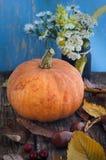 Pomarańczowy dyniowy zakończenie kłama na starym drewnianym stole otaczającym jesień żółtymi liśćmi, mały bukiet ostatni jesień k obrazy stock