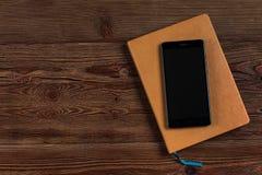 Pomarańczowy dzienniczek z czarnym telefonem obraz stock