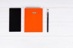 Pomarańczowy dzienniczek z piórem dla robić spotkaniom i telefonowi komórkowemu Obrazy Stock