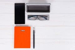 Pomarańczowy dzienniczek z piórem, szkłami i otwartą skrzynką dla szkieł blisko, Fotografia Stock