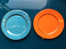 Pomarańczowy i bławy glansowany talerza stojak na zmroku - błękita stół powierzchnia obraz royalty free