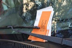 Pomarańczowy i biały mandat za złe parkowanie na przedniej szybie vercal w zdjęcia royalty free
