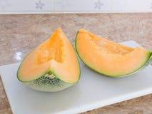 Pomarańczowy japoński melon na białym bloku w kuchni Obraz Royalty Free