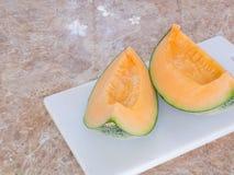 Pomarańczowy japoński melon na białym bloku w kuchni Zdjęcie Royalty Free