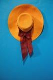 Pomarańczowy kapelusz z faborkiem na błękitnej rocznik ścianie obraz royalty free