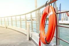 Pomarańczowy lifebuoy cumujący przy poręczem dok fotografia stock