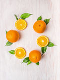 Pomarańczowy owoc wianek z liśćmi na biały drewnianym Zdjęcia Stock