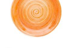 Pomarańczowy round ceramiczny talerz z spirala wzorem na bielu, odosobnionym zdjęcie royalty free