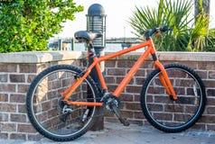 Pomarańczowy rower ściana z cegieł Obraz Stock