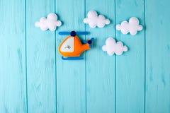 Pomarańczowy rzemiosło helikopter, chmury na błękitnym drewnianym tle z copyspace i Odczuwane handmade zabawki Opróżnia przestrze Zdjęcia Stock