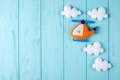 Pomarańczowy rzemiosło helikopter, chmury na błękitnym drewnianym tle z copyspace i Odczuwane handmade zabawki Opróżnia przestrze Zdjęcie Stock