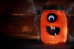 Pomarańczowy słój dekorujący jako Halloweenowy potwór Zdjęcia Stock