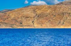 Pomarańczowy skalisty wzgórze i głęboki błękitny ocean zdjęcia stock