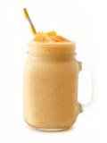 Pomarańczowy smoothie w kamieniarza słoju z słomą odizolowywającą Zdjęcia Stock