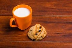 Pomarańczowy szkło mleko z czekoladowym ciastkiem piec z stevia na drewnianym tle Fotografia Royalty Free