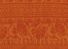 Pomarańczowy tekstylny tło z złotymi wzorami zdjęcia royalty free
