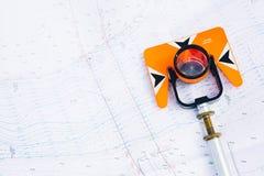 Pomarańczowy theodolite graniastosłup kłama na tła geodezyjnych mapach teren zdjęcie royalty free