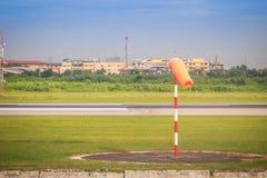 Pomarańczowy windsock lub wiatrowy vane w osoba o umiarkowanych poglądach wiatrze na czerwonym białym słupie przeciw jasnemu nieb obraz stock