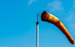 Pomarańczowy windsock w osoba o umiarkowanych poglądach wiatrze na białym słupie przeciw jasny błękitnemu zdjęcia royalty free