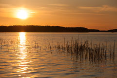 Pomarańczowy zmierzch na jeziorze w Finlandia Obrazy Stock