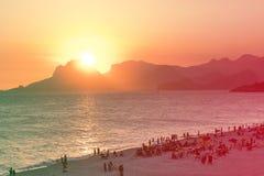 Pomarańczowy zmierzch oceanem w Piratininga, Niteri, z słońca maczaniem behing Gavea kamień w Rio De Janeiro Plaża pełno peop obrazy stock