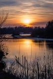 Pomarańczowy zmierzchu chmurnego nieba odbicia jezioro zdjęcia stock